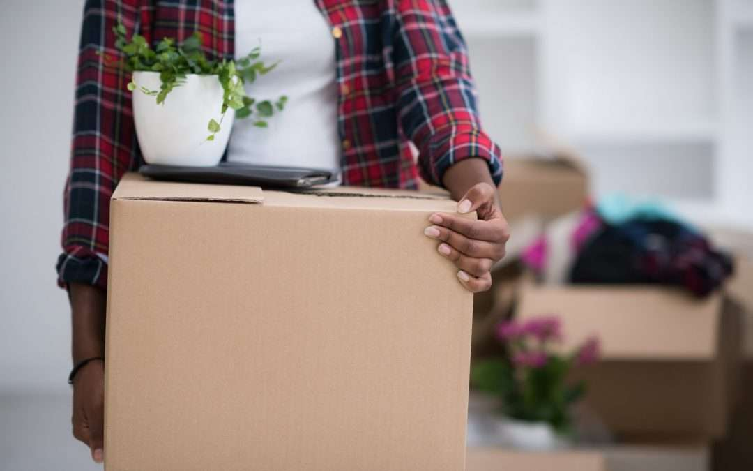 woman holding a moving box with a plant on top